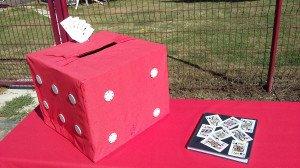 L'urne, un dé rouge géant et le livre d'or décoré de cartes à jouer
